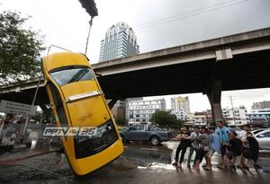 ปชช.ช่วยกู้รถแท็กซี่ตกคูน้ำ หลังฝนกระหน่ำกรุงฯ