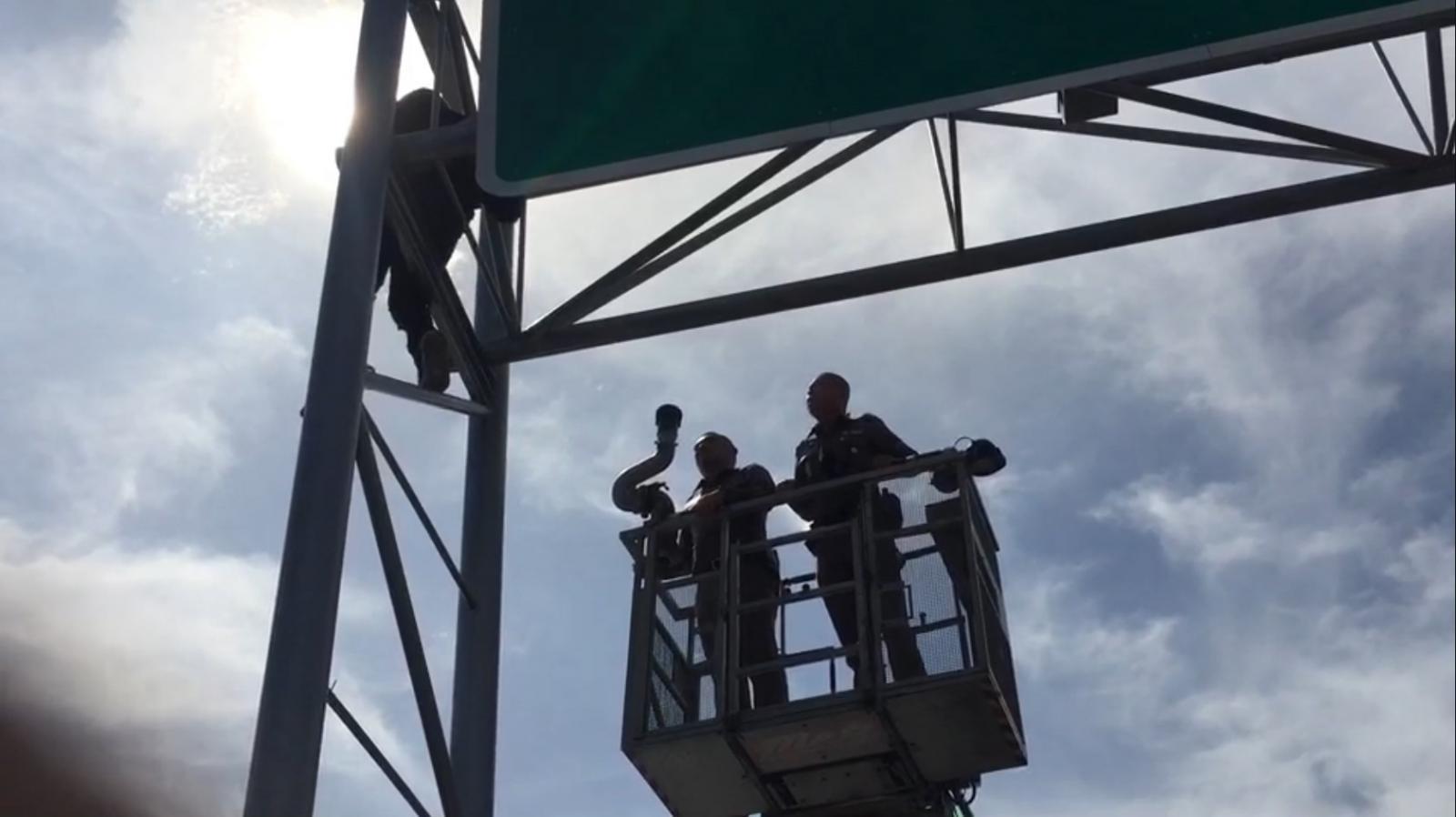 ชายปีนป้ายบอกทาง บนสะพานพระราม 3